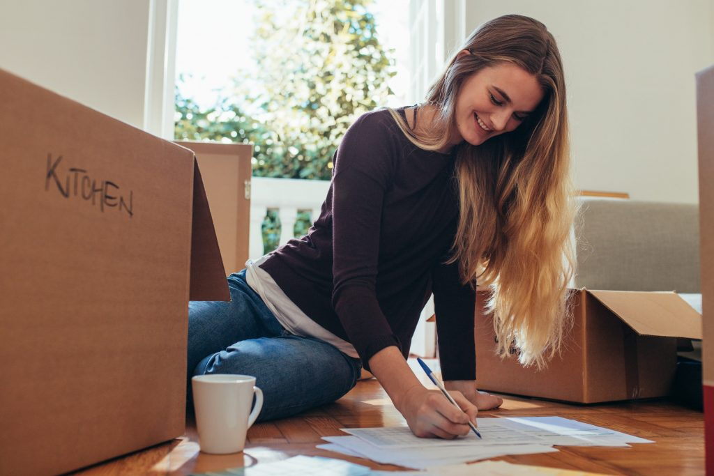Smiling woman sitting on floor making list; background moving boxes