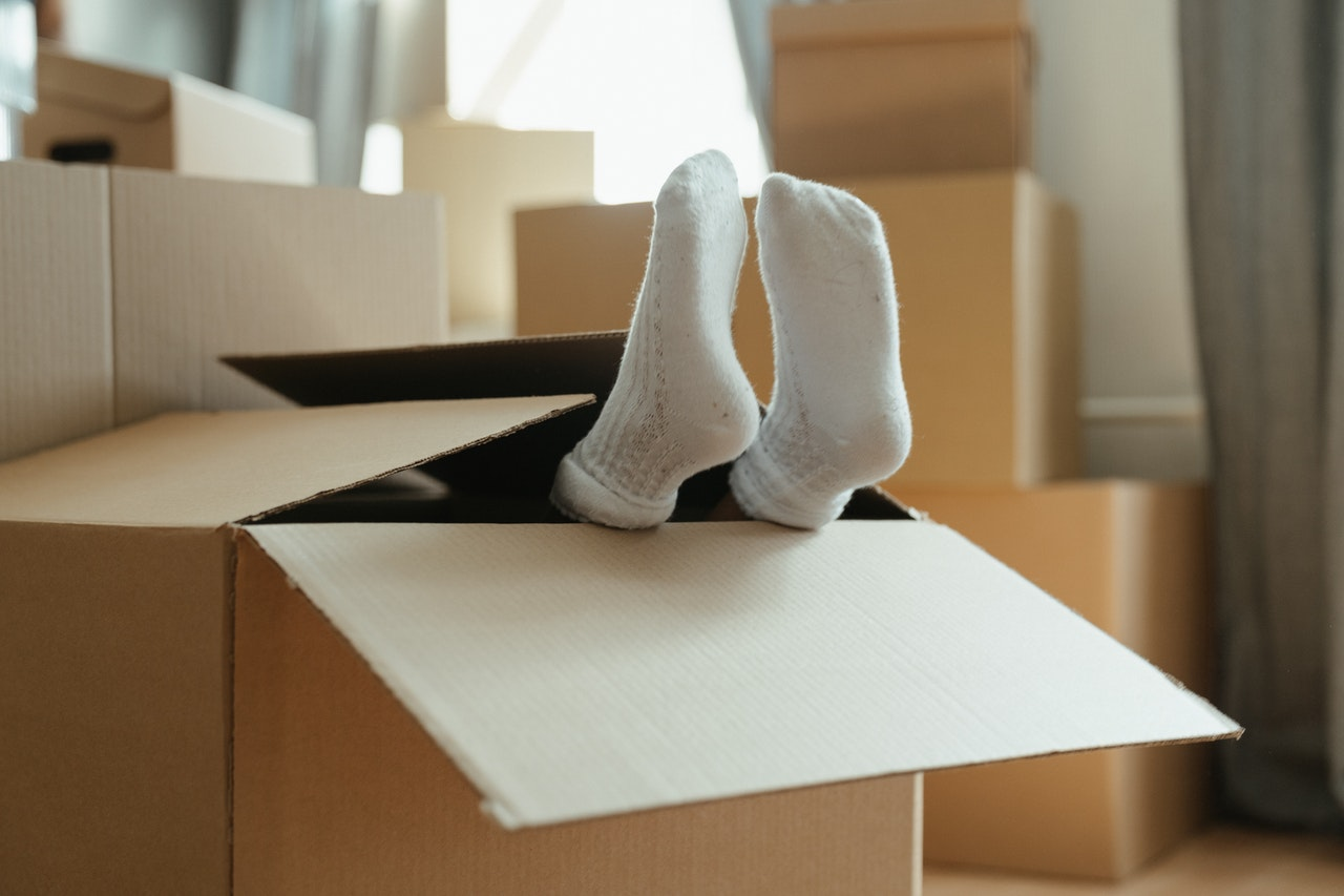 Child's feet in socks sticking out of cardboard box
