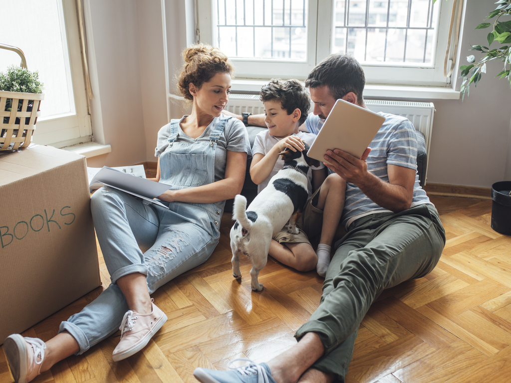 Family sitting on floor in new house with dog